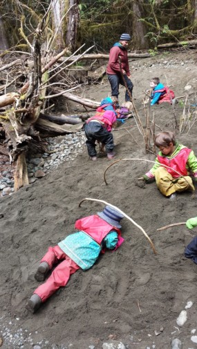 Back at our log jam classroom, we have found nature's sandpit and have made us of it in many ways! Juniper does an army crawl under some rainbow sticks as her friends look on and try it themselves.